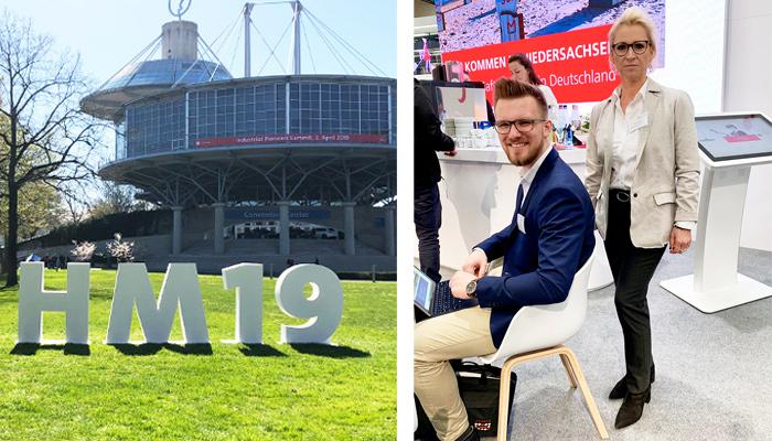#HM19 Zeichen auf dem Messegelände Hannover und das ABAKUS-Messeteam der #HM19 Ulrike Di Carlo und Phillip Hauschild