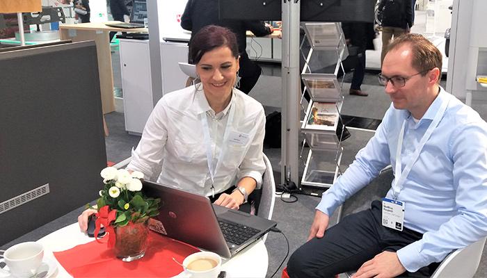 Anna Pianka zeigt einem Interessenten am Laptop Optimierungspotenzial für seine Webseite auf