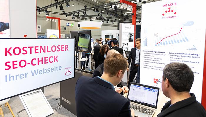 ABAKUS SEO Philipp Ehring und Hannover Messe Fachbesucher beim SEO-Website-Check am Laptop