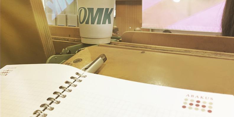 Tisch auf der OMK 2018 mit ABAKUS Schreibheft und Blick auf die OMK-Bühne